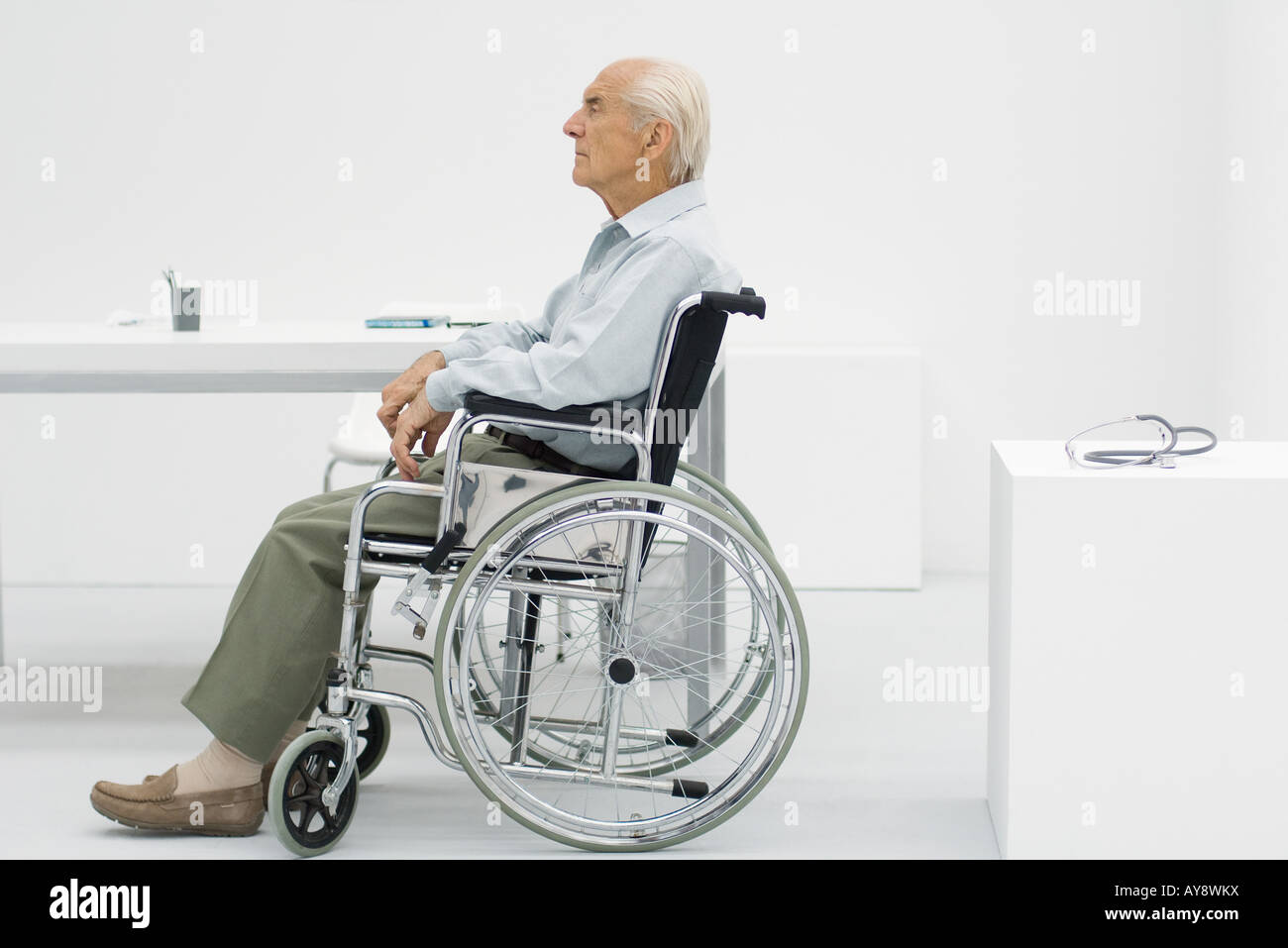 Elderly man sitting in wheelchair in doctor's office, side view - Stock Image