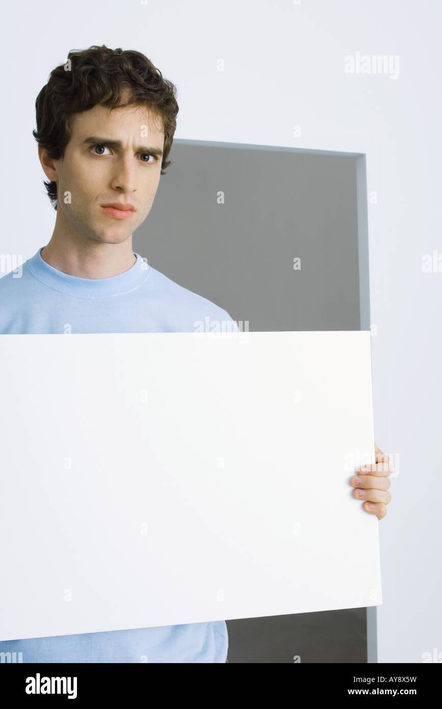 Man holding sign, furrowing brows at camera - Stock Image