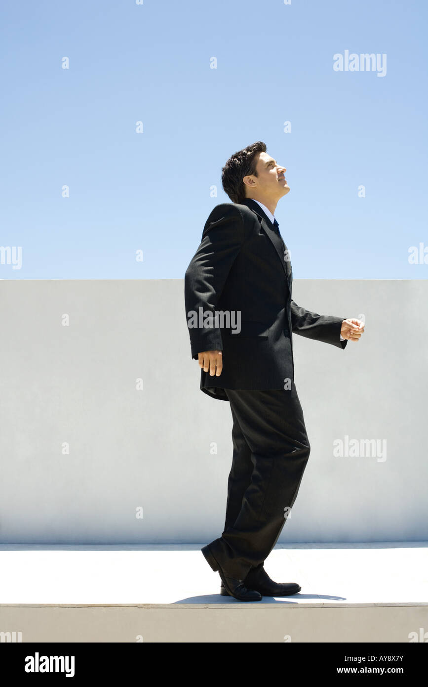 Businessman standing outdoors with one knee bent, looking up - Stock Image