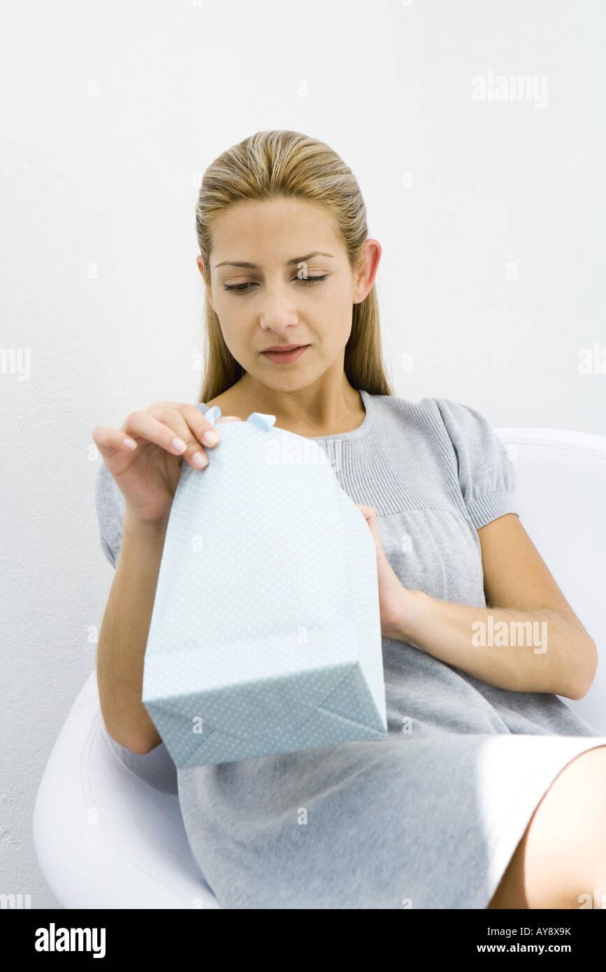 Woman opening gift bag - Stock Image