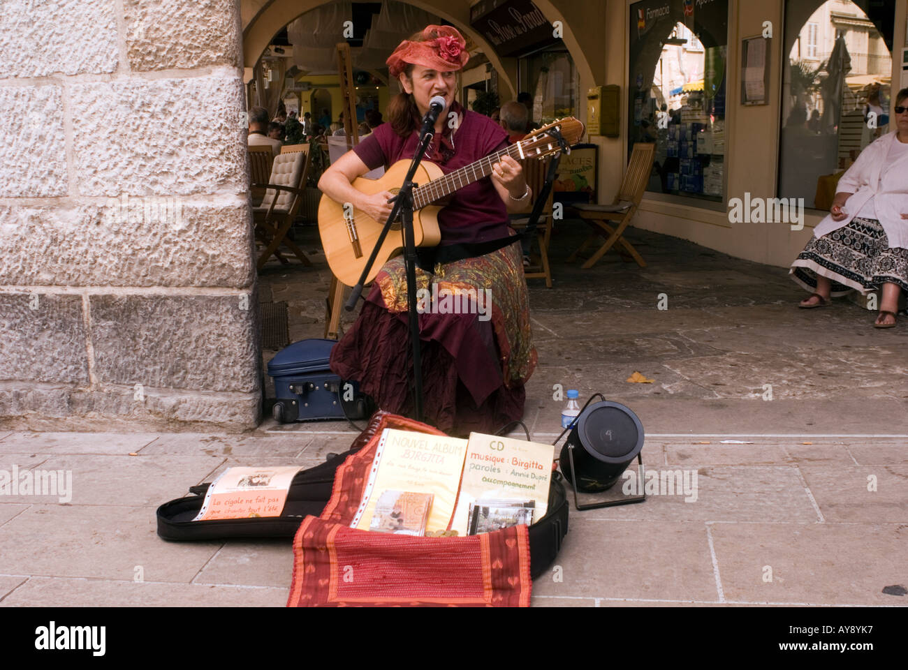 A French woman dressed in Provencal costume playing traditional French folk music. - Stock Image