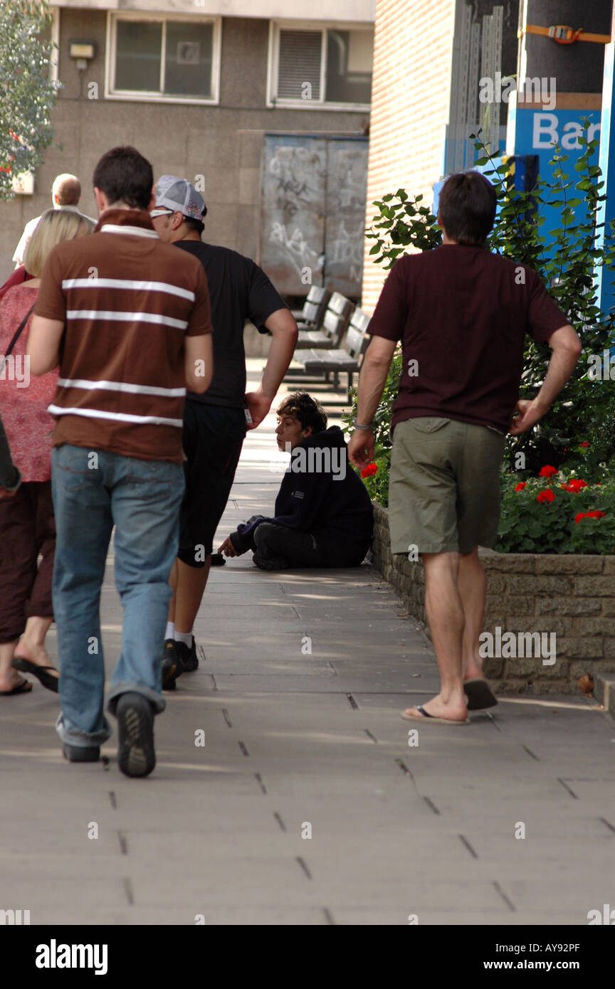 beggar sitting on a sidewalk in London, UK - Stock Image