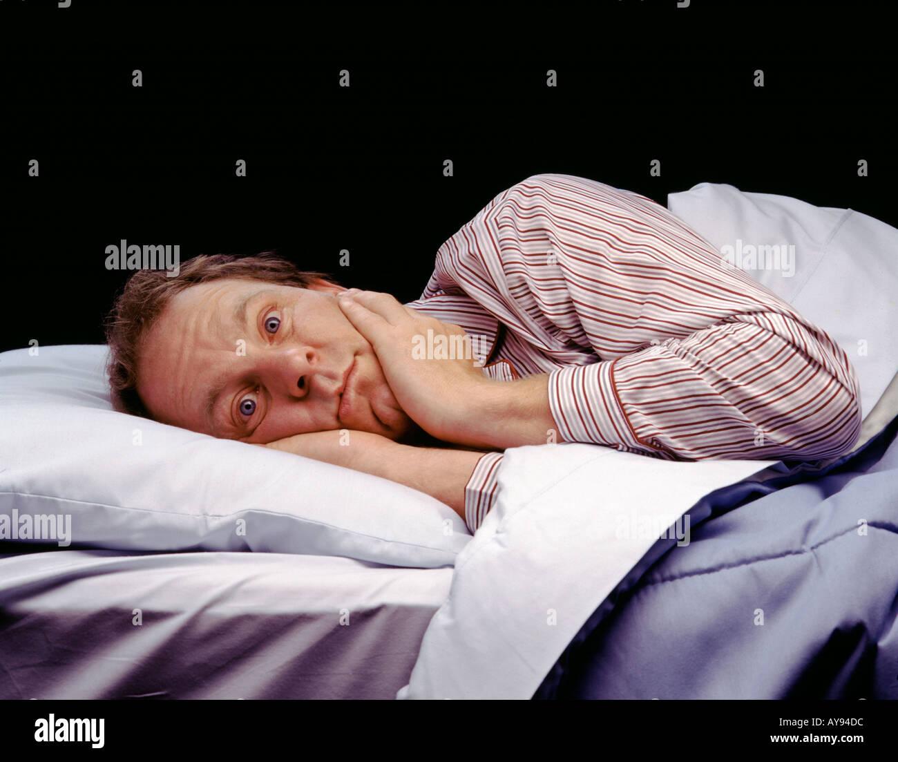 man awake in bed not sleeping - Stock Image