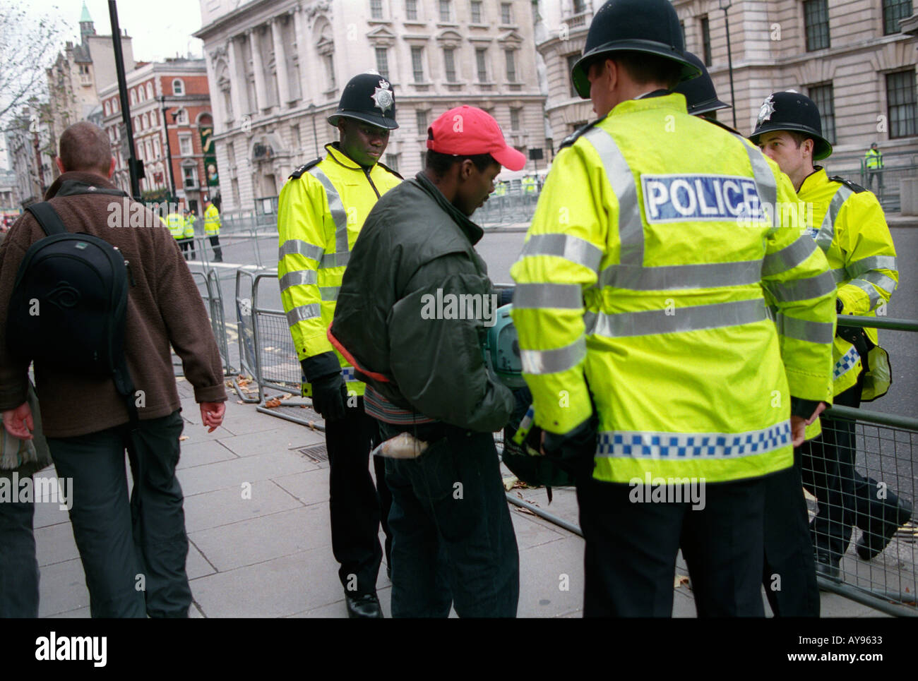 police officers stop and searching young black youth in central London. - Stock Image