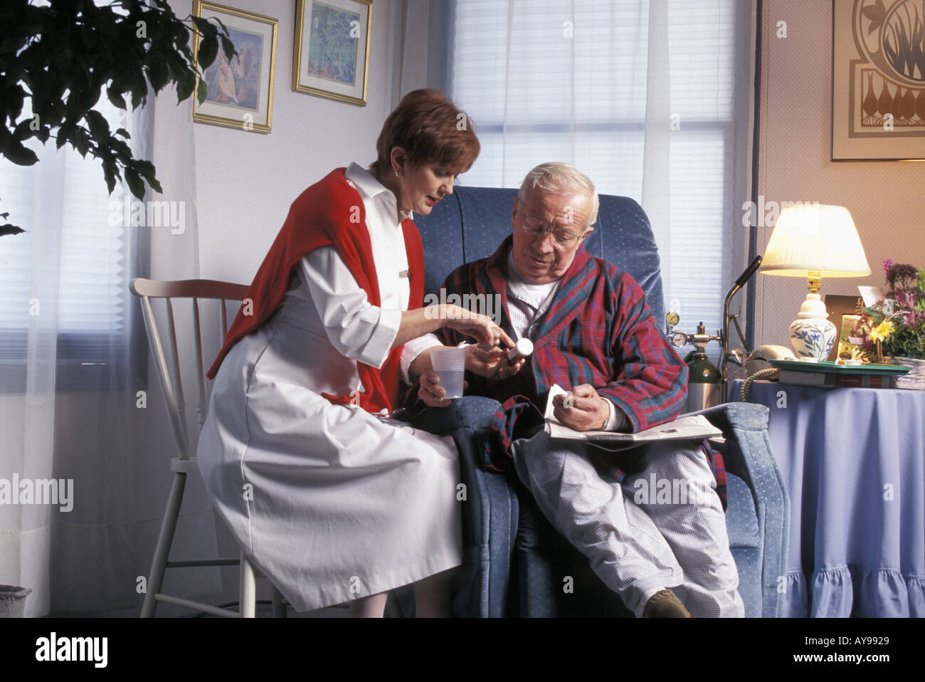 Visiting nurse reviewing medication with homebound senior male patient - Stock Image