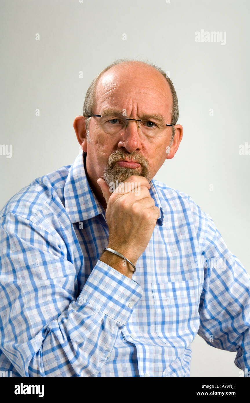 60 year old white man with a a goatee beard and a  facial expression depicting querulousness Stock Photo