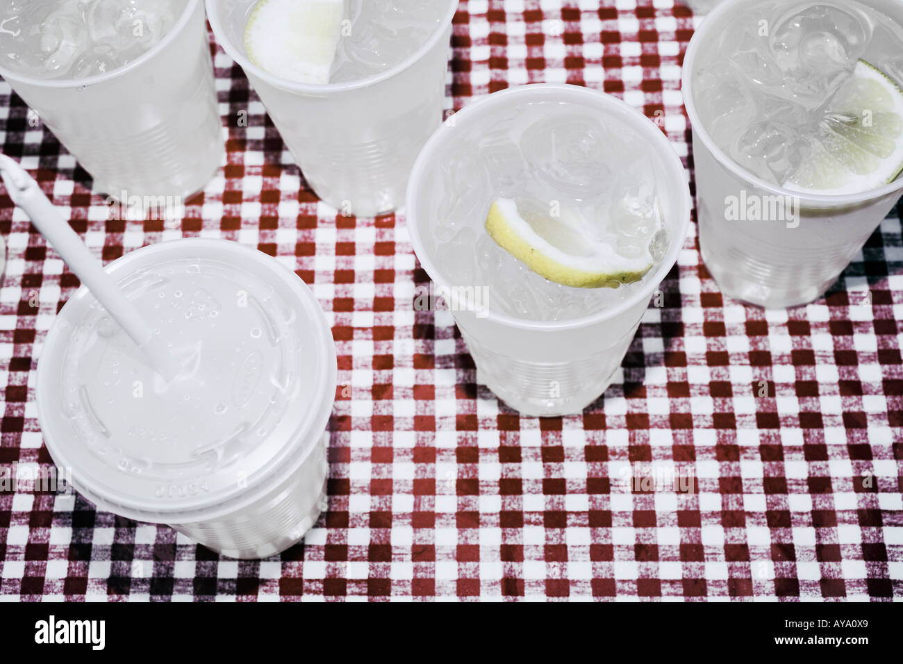 Plastic Cups Filled With Lemonade Standing On Checked Tablecloth - Stock Image