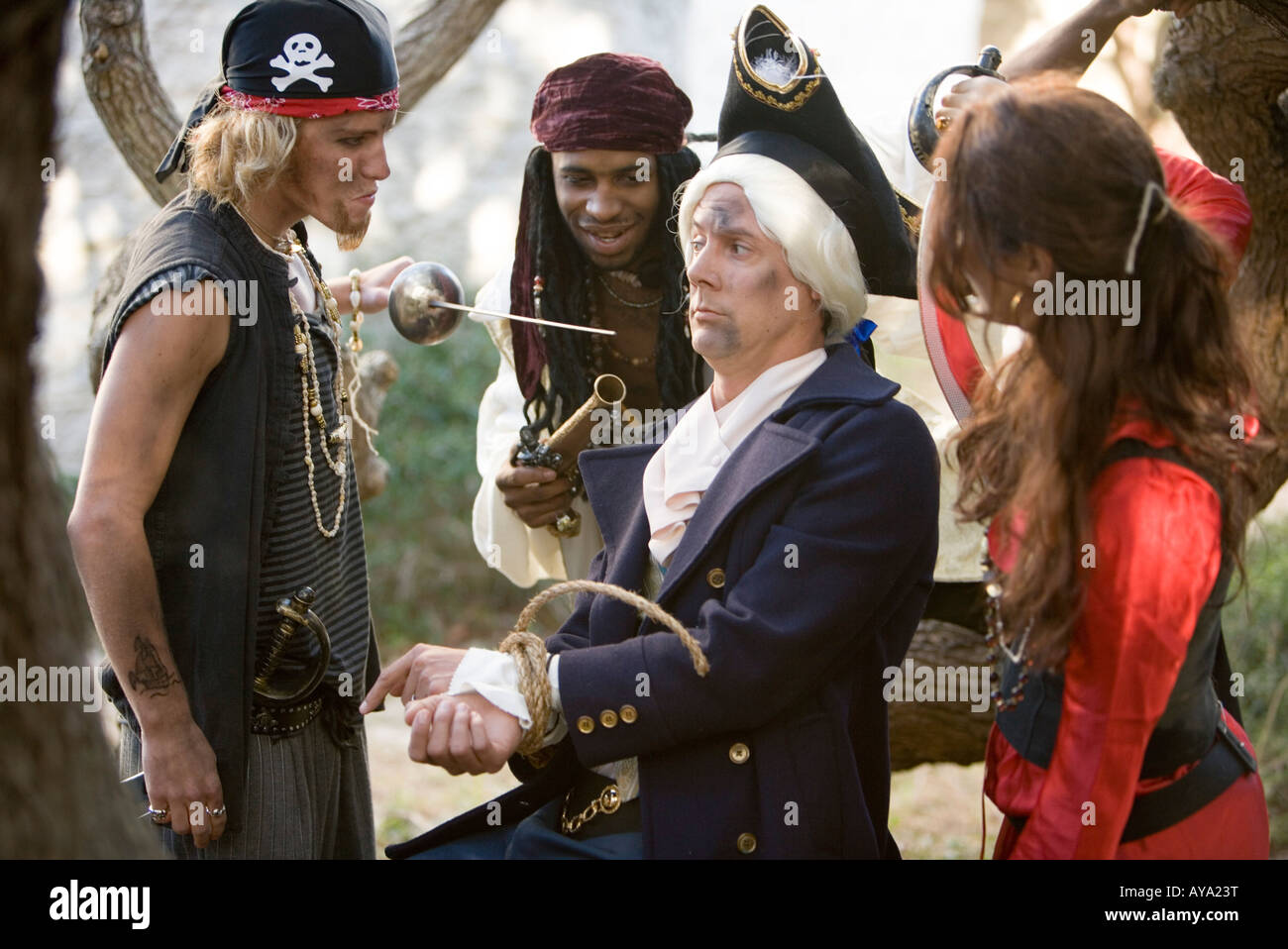 View of armed pirates holding a navy officer captive and threatening him with a sword and a gun - Stock Image