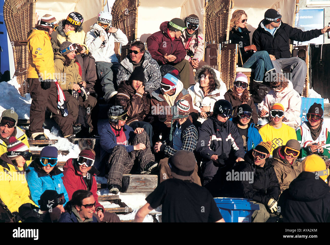 Men, women and children in skiwear and masks sitting in Surselva, Grisons, Switzerland - Stock Image