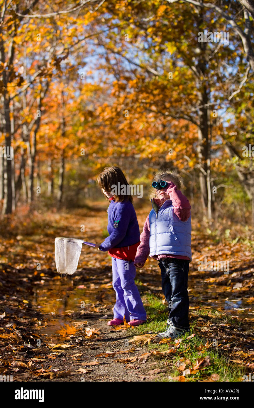 Two young girls (ages 4 and 6) on a woodland trail in Biddeford, Maine - Stock Image