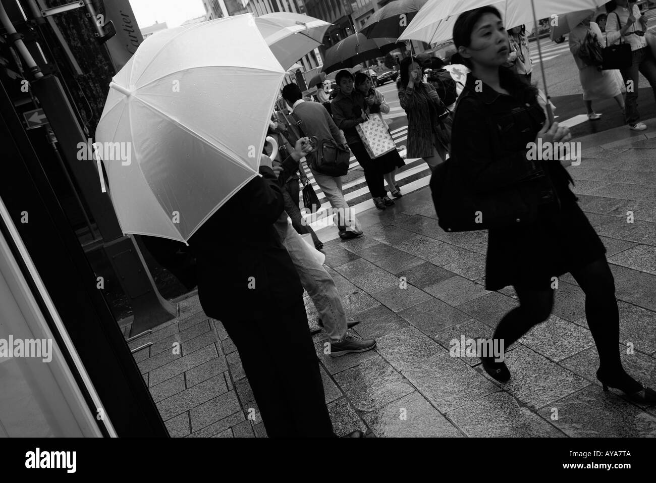 Asia Tokyo Japan Shoppers carrying umbrellas walking past department store window on rainy afternoon in Ginza District Stock Photo