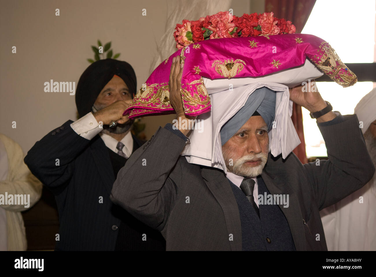 Sikhs inside temple (Gurdwara) with the Holy scripture on the festival of Vaisakhi, Siri Guru Singh Sabha, Hounslow, - Stock Image