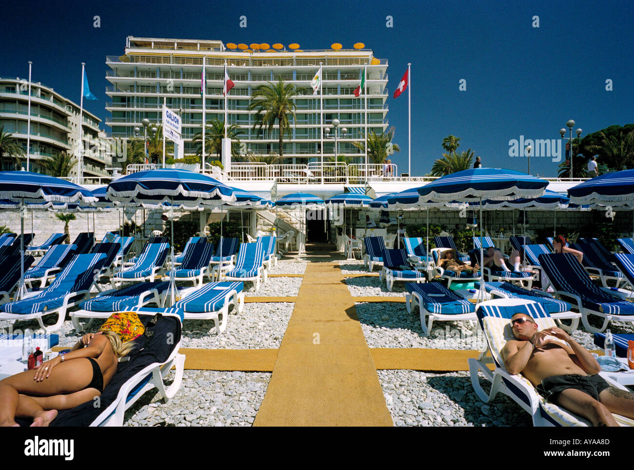 On a pay beach at Nice on the French Riviera the blue theme of the umbrellas and loungers marries well with the blue sky - Stock Image