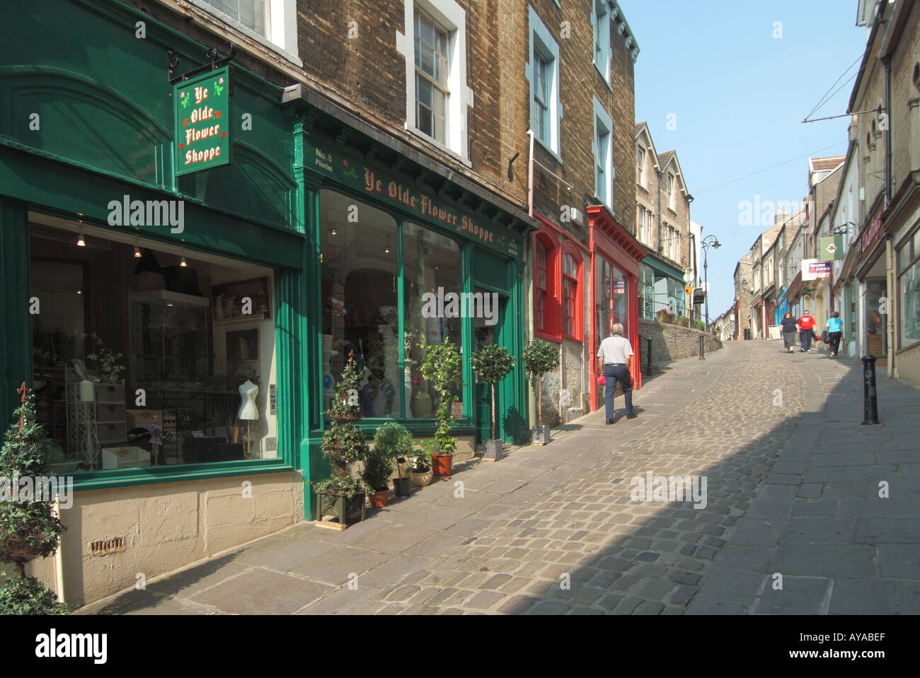 Frome a quaint narrow hilly side street housing a selection of small shops and eating venues with dwellings above Stock Photo