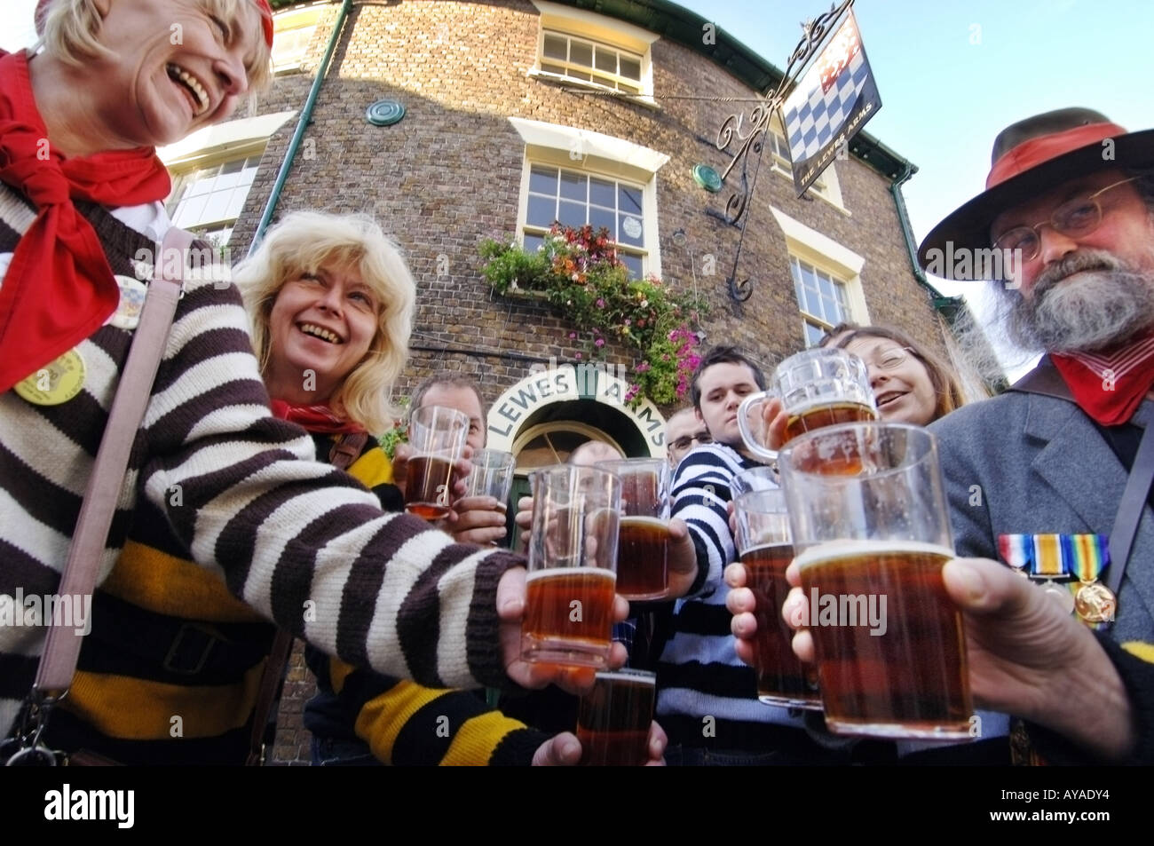 A crowd of regulars at a traditional Sussex pub raise a glass of their favourite brew. - Stock Image