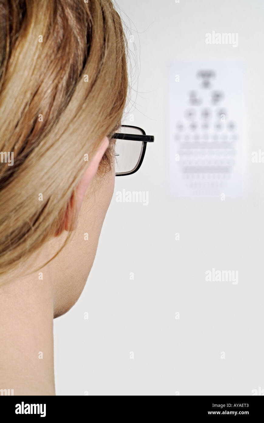 Woman Having Her Eye Sight With Spectacles Checked by Reading a Snellen Chart on an Opticians Wall - Stock Image