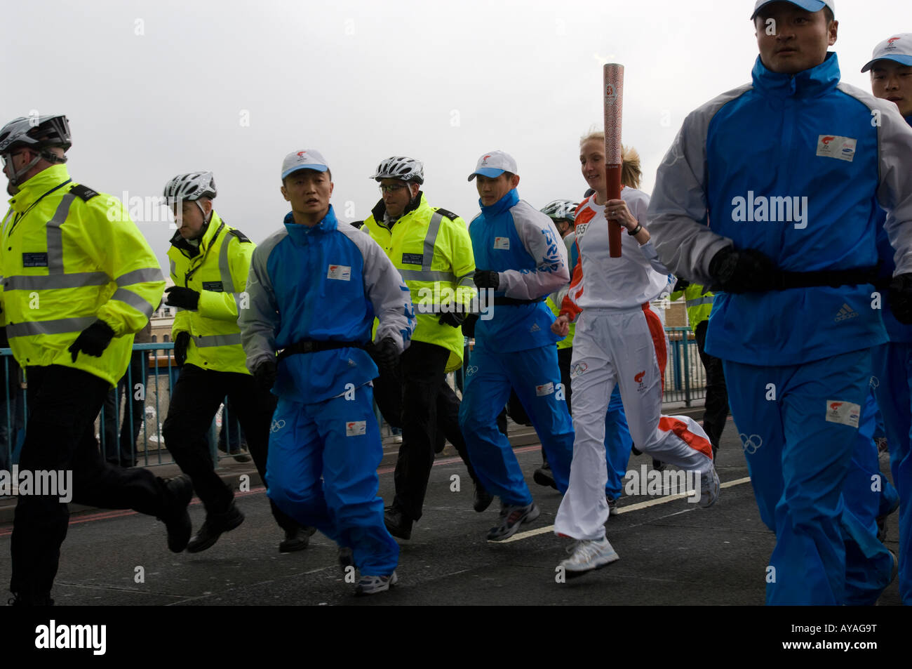 Paula Radcliffe with Olympic Torch on Tower Bridge during relay through London.  Chinese security and British Police. Stock Photo