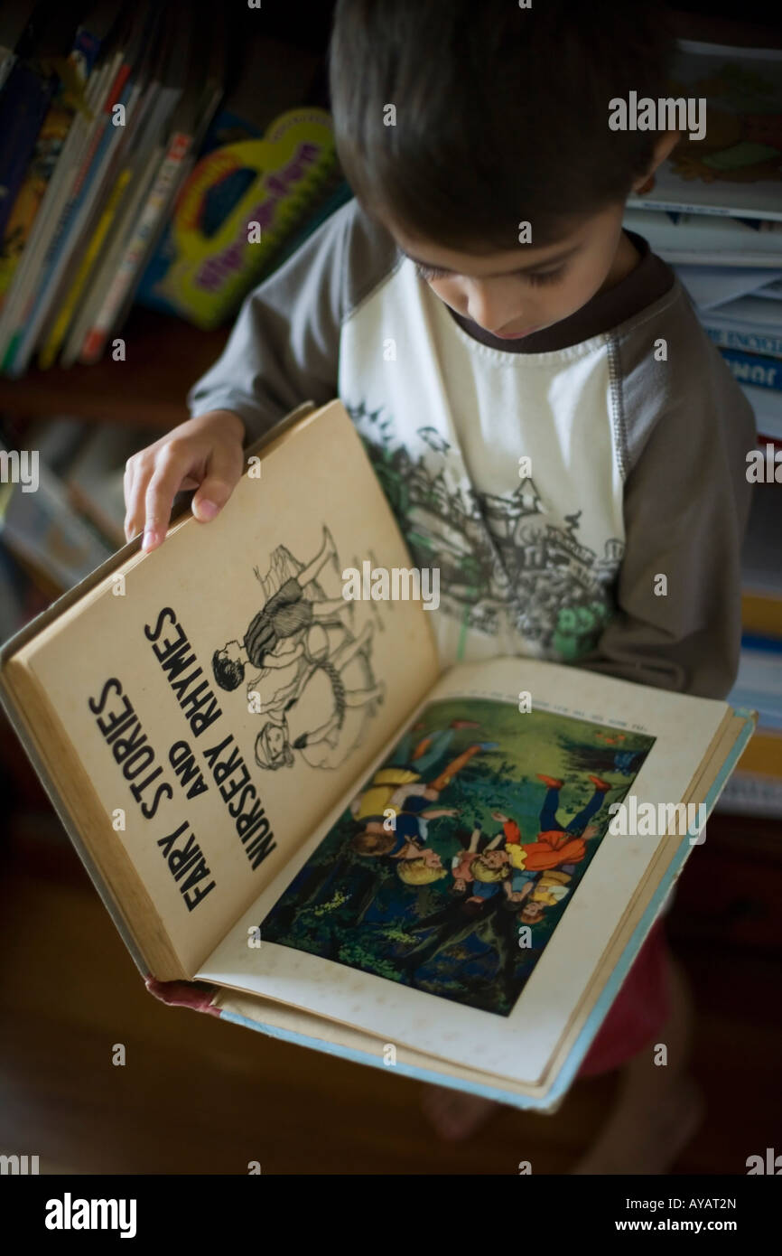 Boy aged six years reads book of Fairy Tales and Nursery Rhymes Stock Photo