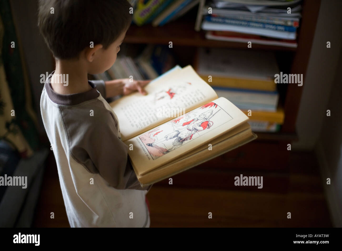 Boy aged six years reads book of Fairy Tales and Nursery Rhymes - Stock Image