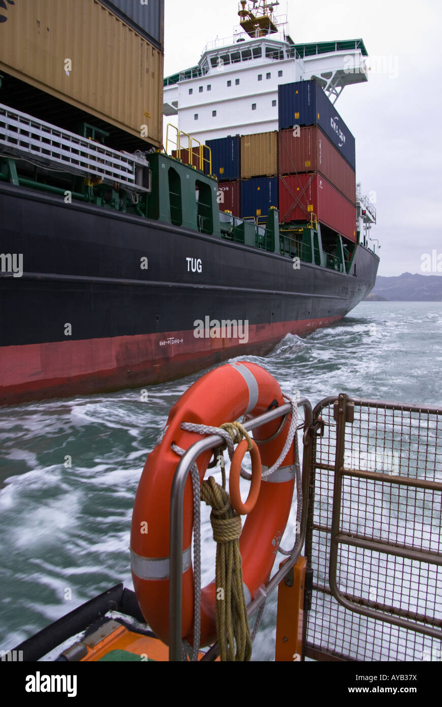 The aft end of a container ship as viewed from the pilot boat coming alongside that ship to collect the pilot Stock Photo