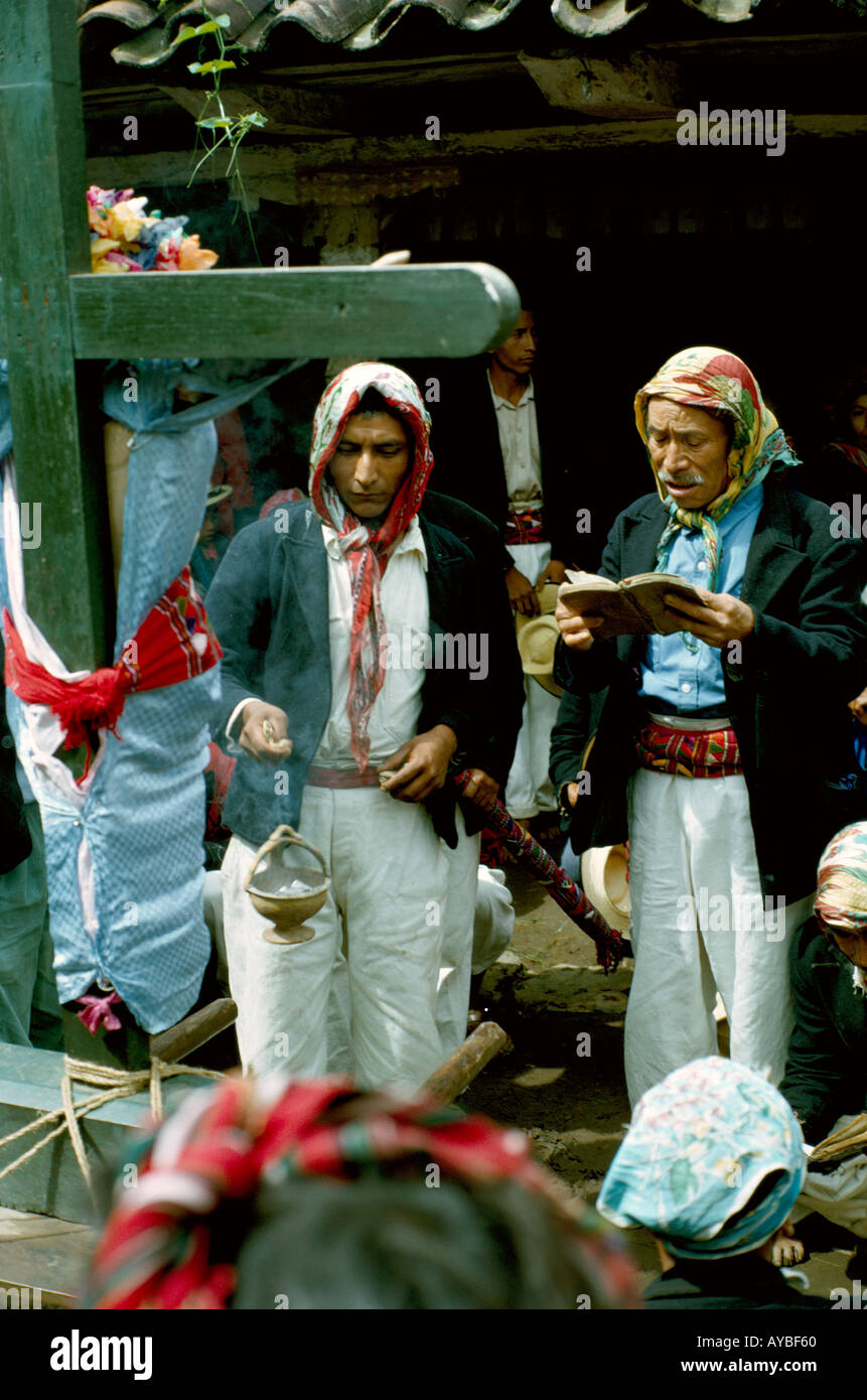 Guatemala Ixil Maya Indian men praying while procession stopped at a cofradia religious brotherhood in Nebaj Dept El Quiche - Stock Image