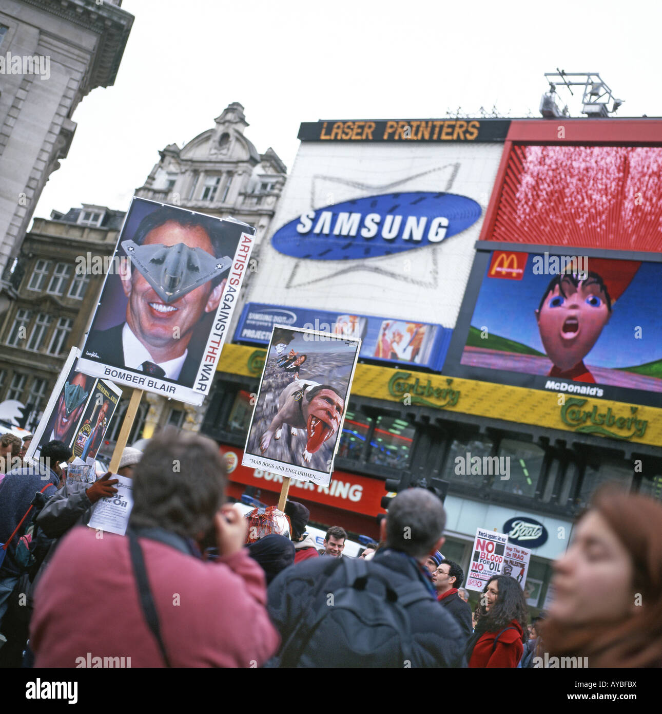 Demonstrators with posters of Bush and Blair at Picadilly Circus during the Anti War March on 15th February 2003 - Stock Image