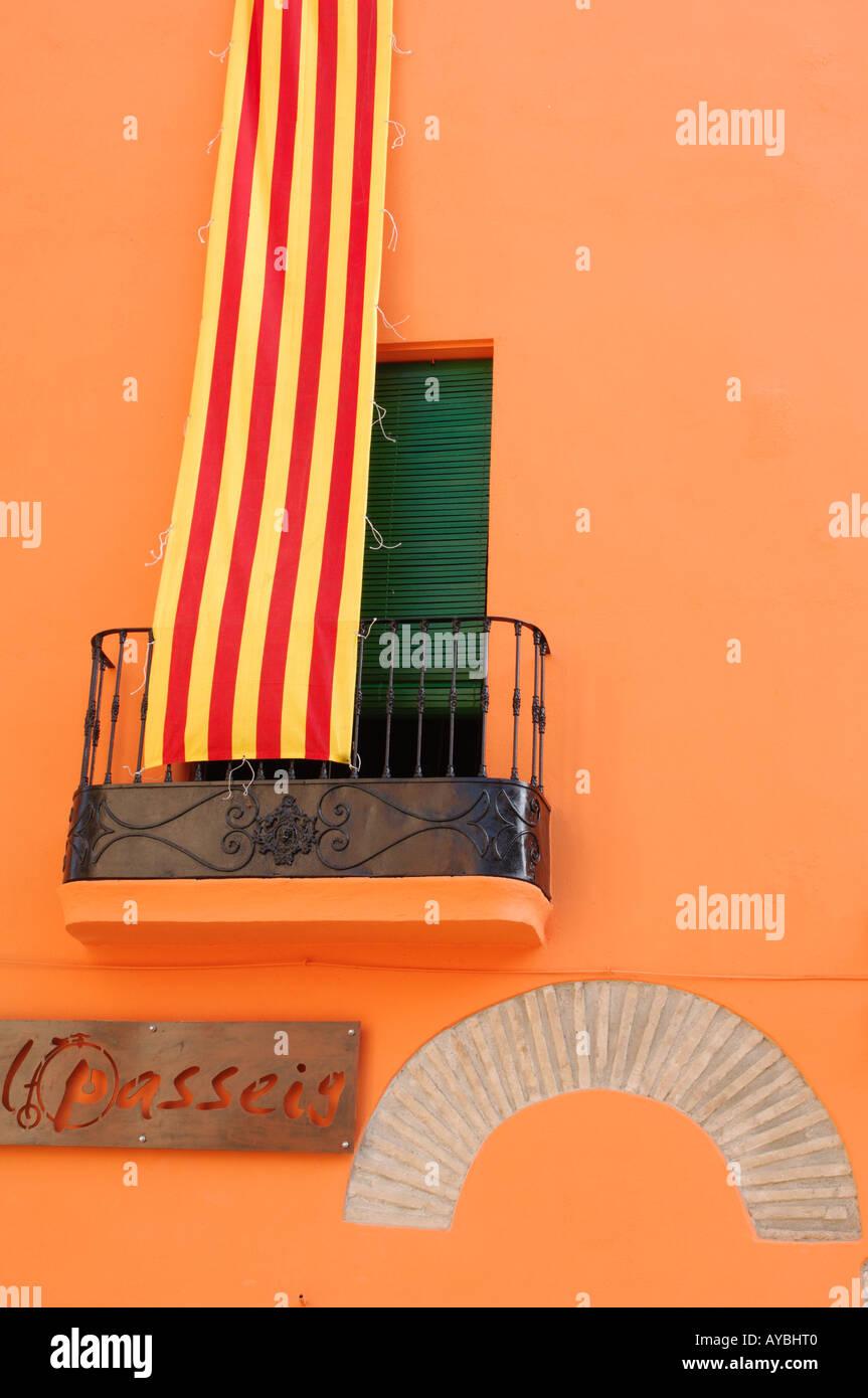 catalonian banner haging down walls of orange terracotta coloured building castello d empuries costa brava spain - Stock Image