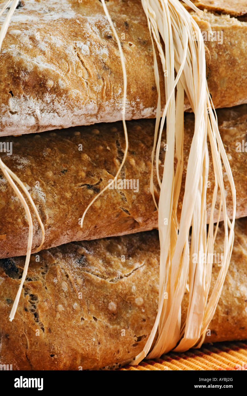 Crisp Italian olive bread stacked and bound together with rafia - Stock Image