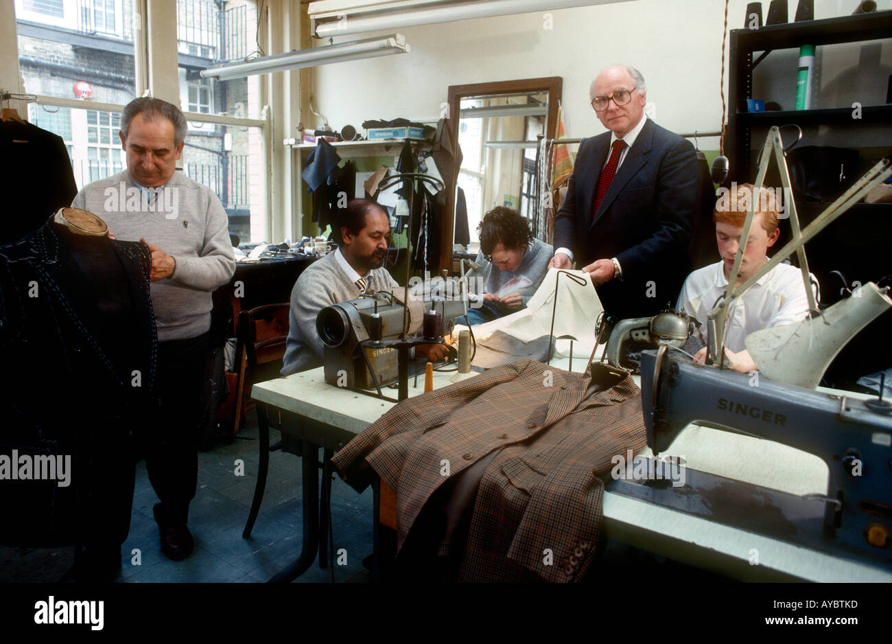 Savile Row Robert Bright Master Tailor seen here with his staff upstairs in the bespoke tailoring shop Wells of Mayfair London - Stock Image