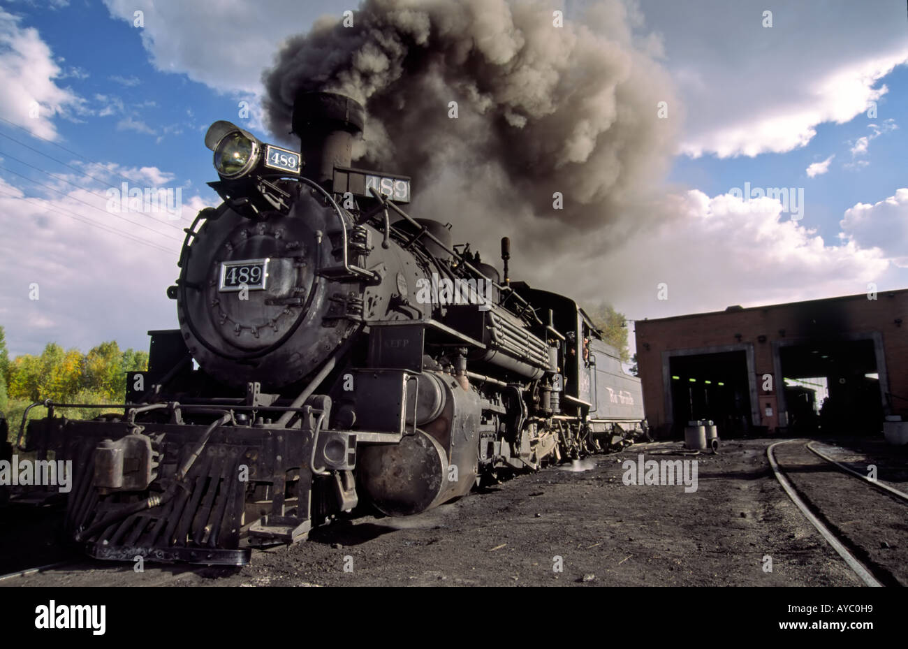 With much smoke, coal-fired steam engine 489 pulls out of the roundhouse in  Chama, New Mexico.