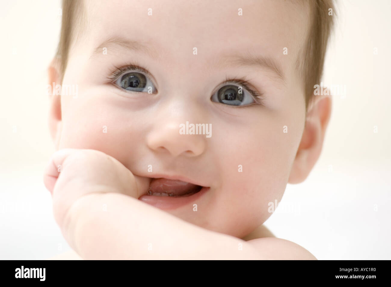 6 month old caucasian baby girl smiling with finger in her mouth - Stock Image