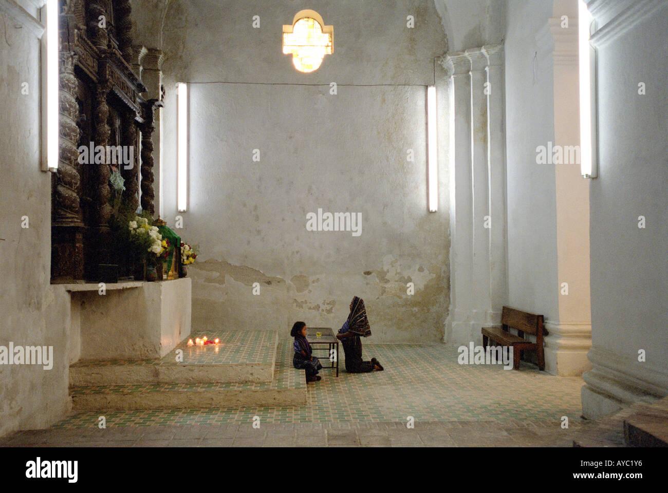 Woman and Child at Prayer, Church Interior, Santiago, Lake Atitlan, Guatemala - Stock Image