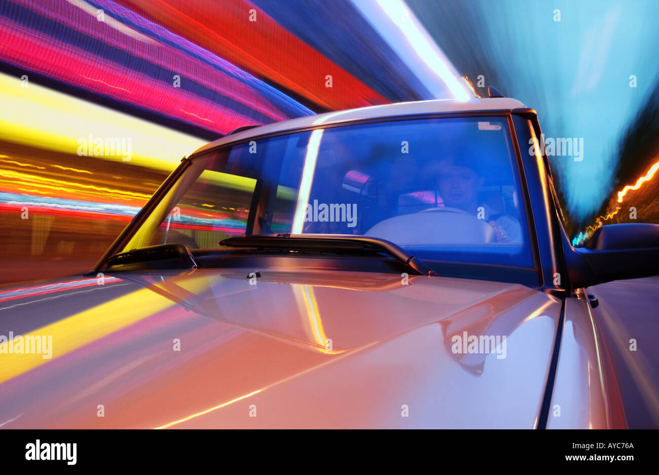Hood and windshield of suv driving at night with colorful lights blurring in background - Stock Image