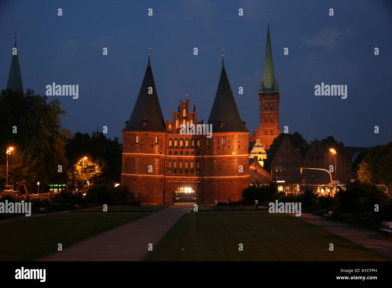 The famous Holstentor ('Holsten Gate') at night , part of the medieval fortifications of Lübeck in - Stock Image