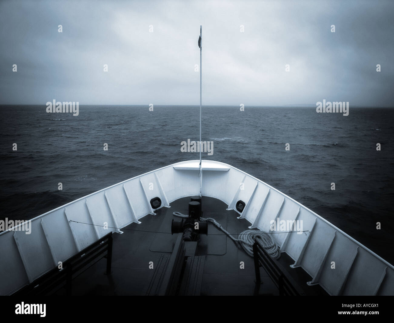 The bow of a ship headed out to stormy overcast sea - Stock Image