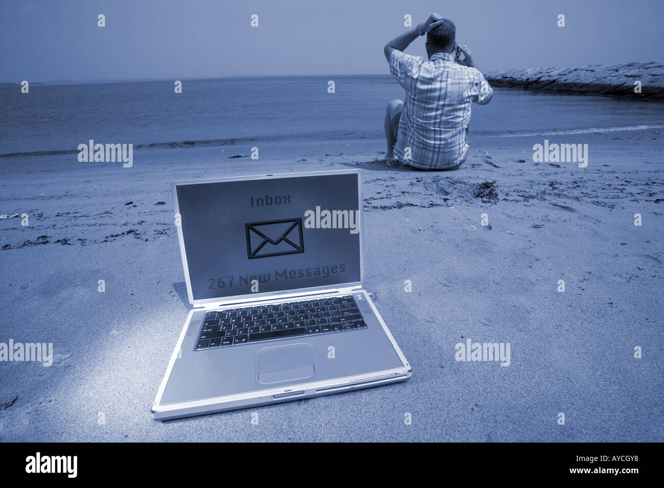 Man returning calls overworked on beach with cell phone and laptop on vacation - Stock Image