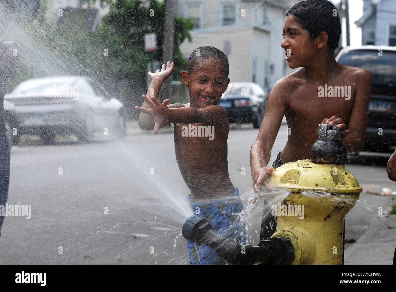Children cooling off during summer heat wave in an urban city global warming concept - Stock Image
