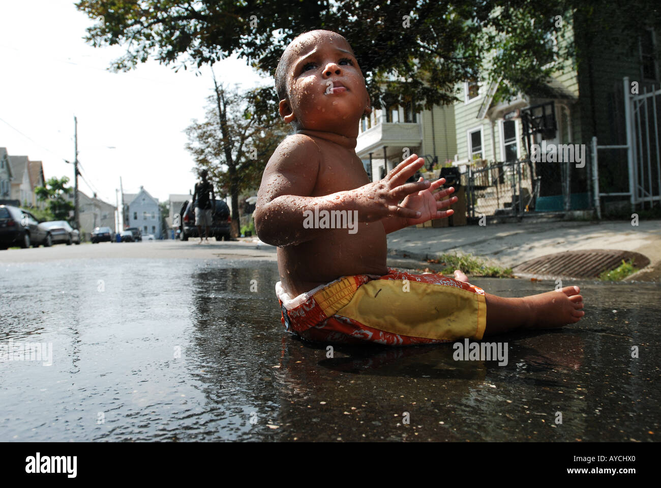 Child cooling off during summer heat wave in an urban city global warming concept - Stock Image