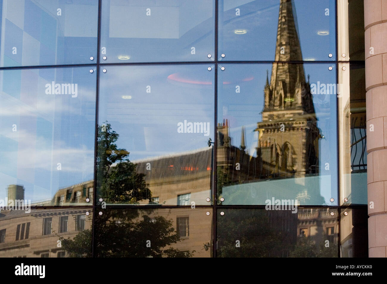 Reflections of St Paul`s church through the large front windows of the Overgate shopping mall windows in Dundee,UK - Stock Image