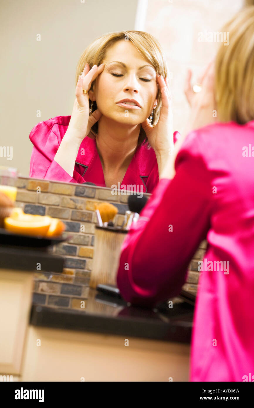 Woman massaging her head in mirror Stock Photo