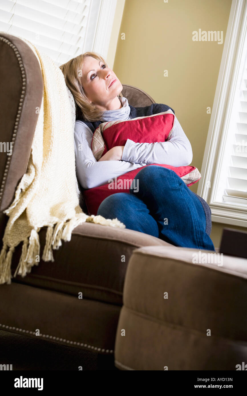 Woman sitting on couch - Stock Image