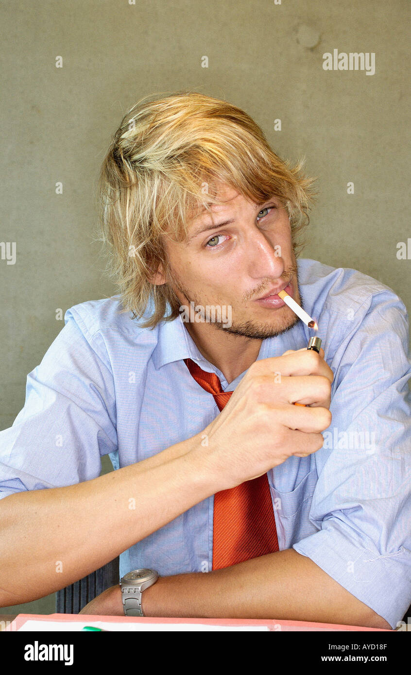 Office worker smoking a cigarette - Stock Image