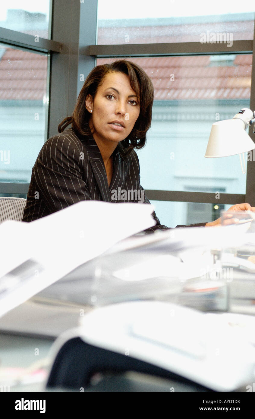 Businesswoman at messy desk - Stock Image