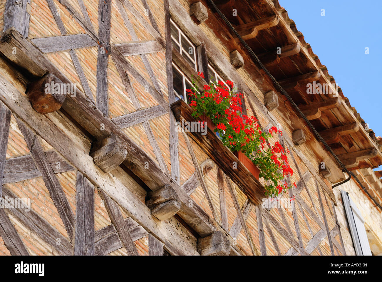 Half-timbered house with window box, Lauzerte, France. Low angle view. - Stock Image