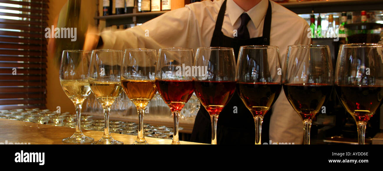 Contemporary bar shot of barman pouring wine into glasses for a tasting - Stock Image