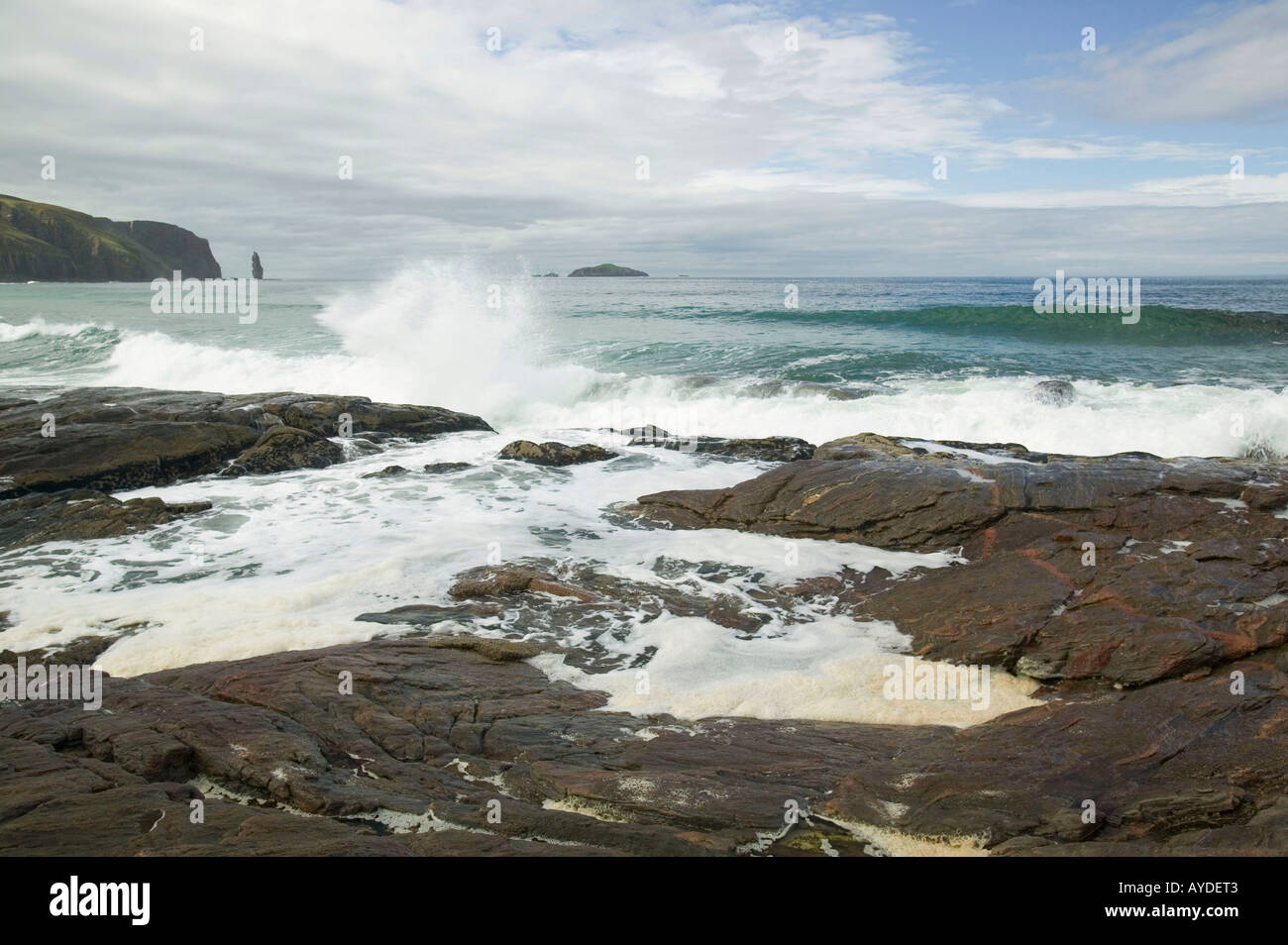 waves crashing against a rocky outcrop in Sandwood Bay, Sutherland, Scotland, UK - Stock Image