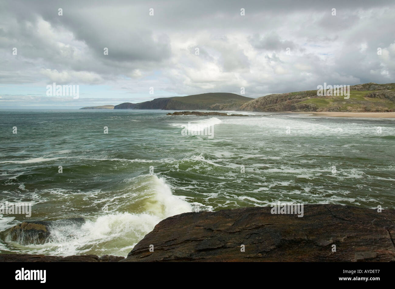 waves crashing against a rocky outcrop in Sandwood Bay, Sutherland, Scotland, UK Stock Photo