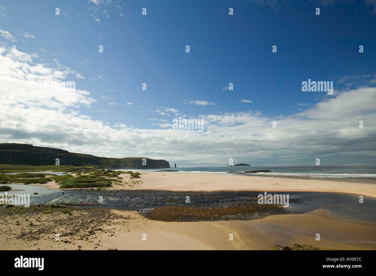 The outflow of Sandwood loch with peat stained water and Sandwood Bay, Sutherland, Scotland, UK - Stock Image