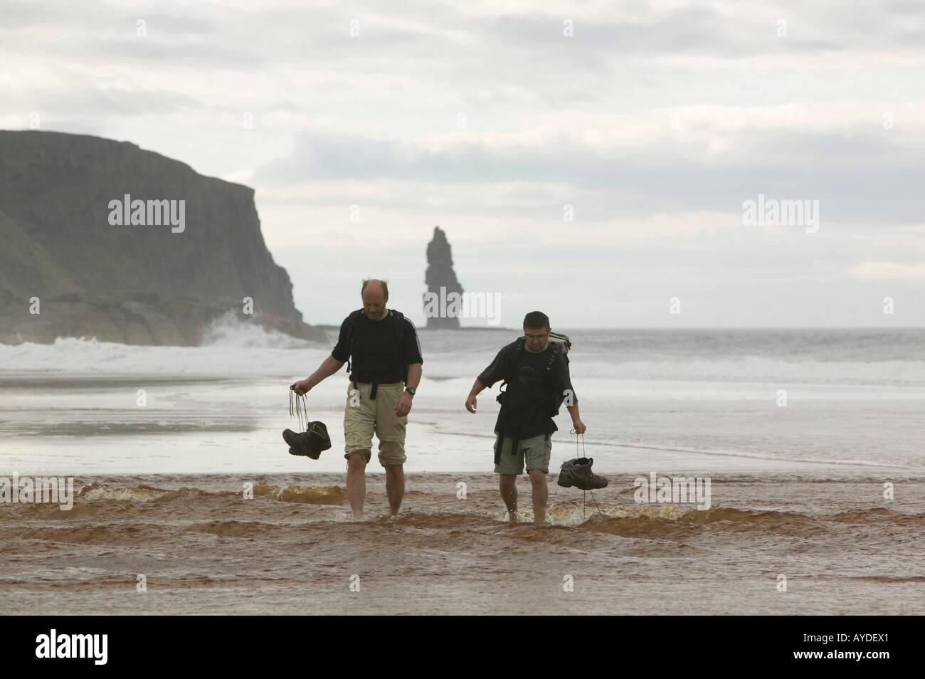 Hikers crossing the outflow of Sandwood Loch into the sea across Sandwood Beach, Sutherland, Scotland, UK - Stock Image