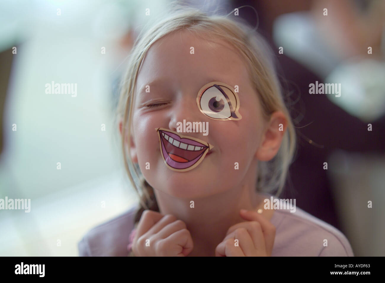 seven year old girl with stick on mouth and eye - Stock Image